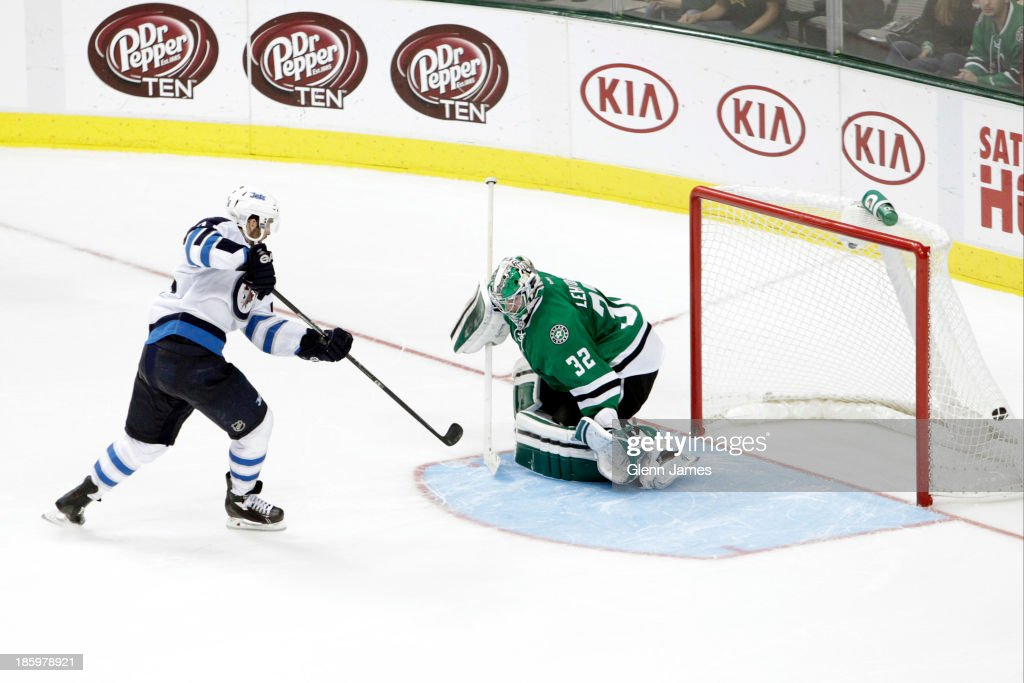 <a gi-track='captionPersonalityLinkClicked' href=/galleries/search?phrase=Andrew+Ladd&family=editorial&specificpeople=228452 ng-click='$event.stopPropagation()'>Andrew Ladd</a> #16 of the Winnipeg Jets gets a shootout winning goal against <a gi-track='captionPersonalityLinkClicked' href=/galleries/search?phrase=Kari+Lehtonen&family=editorial&specificpeople=211612 ng-click='$event.stopPropagation()'>Kari Lehtonen</a> #32 of the Dallas Stars at the American Airlines Center on October 26, 2013 in Dallas, Texas.