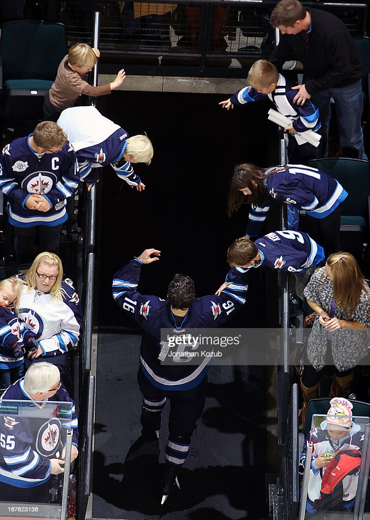 <a gi-track='captionPersonalityLinkClicked' href=/galleries/search?phrase=Andrew+Ladd&family=editorial&specificpeople=228452 ng-click='$event.stopPropagation()'>Andrew Ladd</a> #16 of the Winnipeg Jets high fives fans as he leaves the ice after receiving first star honors following a 5-4 shootout victory over the San Jose Sharks at the MTS Centre on November 10, 2013 in Winnipeg, Manitoba, Canada.