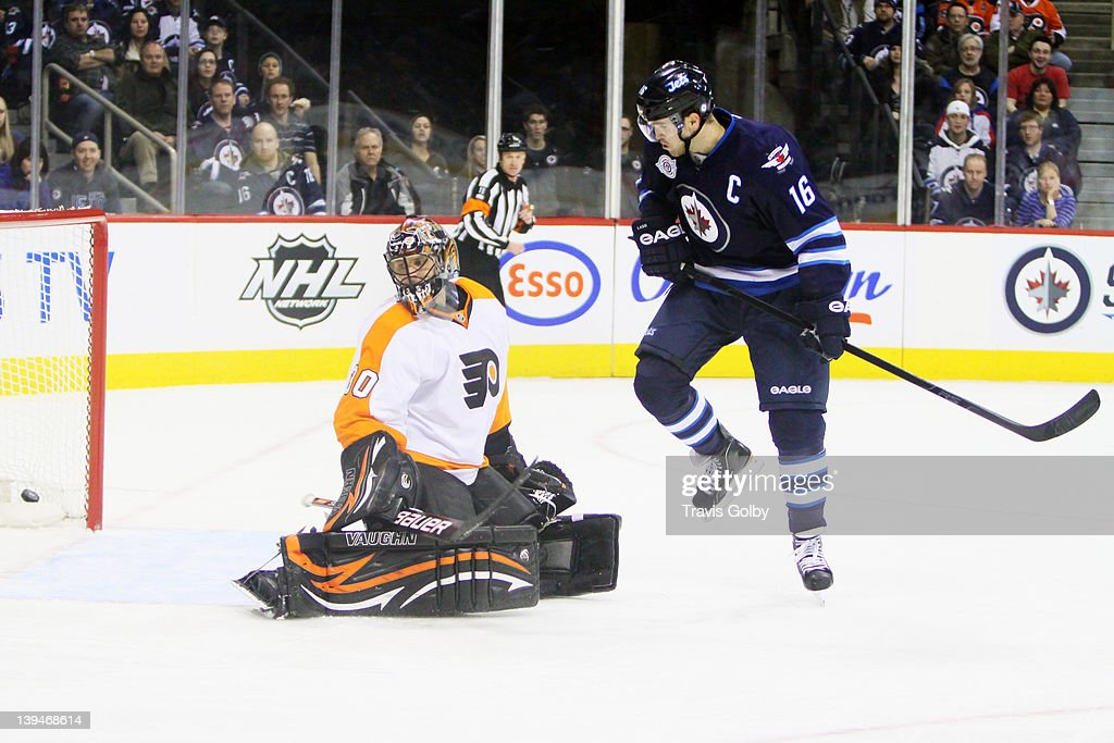 Andrew Ladd #16 of the Winnipeg Jets jumps out of the way as the puck goes into the net behind goaltender Ilya Bryzgalov #30 of the Philadelphia Flyers during first period action at the MTS Centre on February 21, 2012 in Winnipeg, Manitoba, Canada.