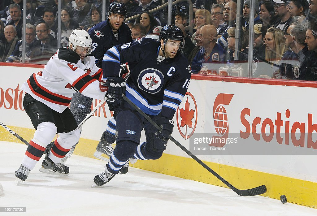 Andrew Ladd #16 of the Winnipeg Jets plays the puck along the boards as Andy Greene #6 of the New Jersey Devils gives chase during first-period action at the MTS Centre on February 28, 2013 in Winnipeg, Manitoba, Canada. The Jets defeated the Devils 3-1.