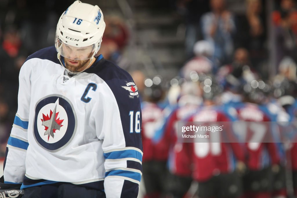<a gi-track='captionPersonalityLinkClicked' href=/galleries/search?phrase=Andrew+Ladd&family=editorial&specificpeople=228452 ng-click='$event.stopPropagation()'>Andrew Ladd</a> #16 of the Winnipeg Jets ponders a loss as the Colorado Avalanche celebrate behind him at the Pepsi Center on October 27, 2013 in Denver, Colorado. The Avalanche defeated the Jets 3-2.