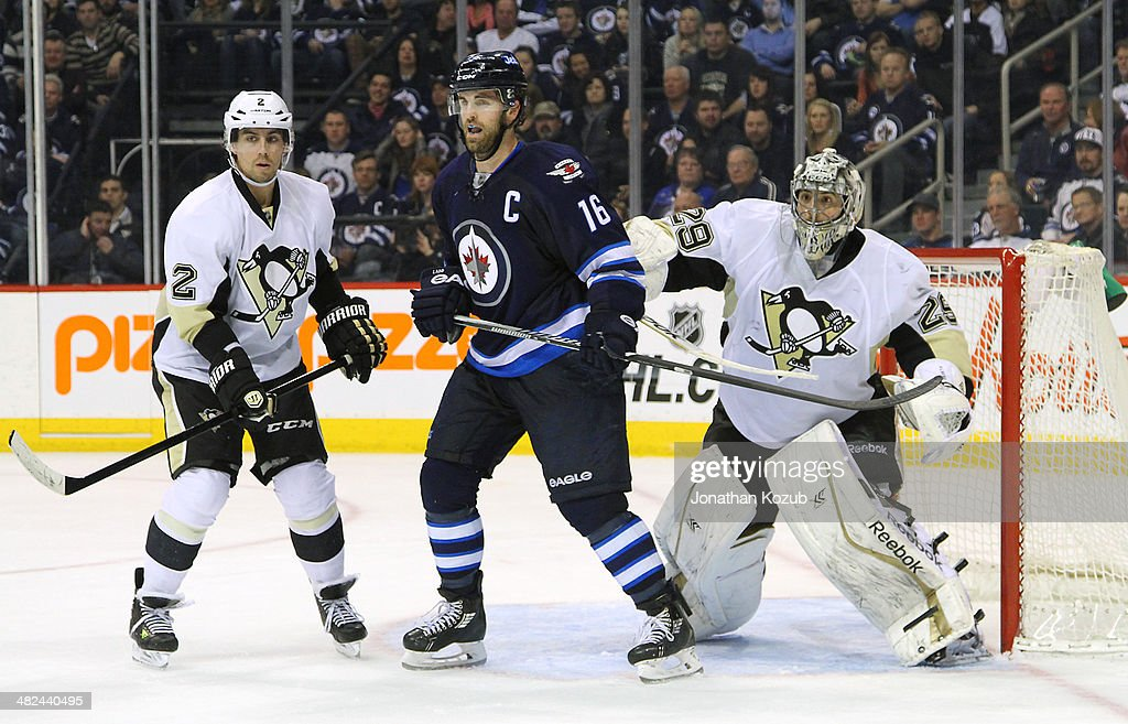 <a gi-track='captionPersonalityLinkClicked' href=/galleries/search?phrase=Andrew+Ladd&family=editorial&specificpeople=228452 ng-click='$event.stopPropagation()'>Andrew Ladd</a> #16 of the Winnipeg Jets positions himself between <a gi-track='captionPersonalityLinkClicked' href=/galleries/search?phrase=Matt+Niskanen&family=editorial&specificpeople=2106633 ng-click='$event.stopPropagation()'>Matt Niskanen</a> #2 and goaltender <a gi-track='captionPersonalityLinkClicked' href=/galleries/search?phrase=Marc-Andre+Fleury&family=editorial&specificpeople=233779 ng-click='$event.stopPropagation()'>Marc-Andre Fleury</a> #29 of the Pittsburgh Penguins during third-period action at the MTS Centre on April 3, 2014 in Winnipeg, Manitoba, Canada.
