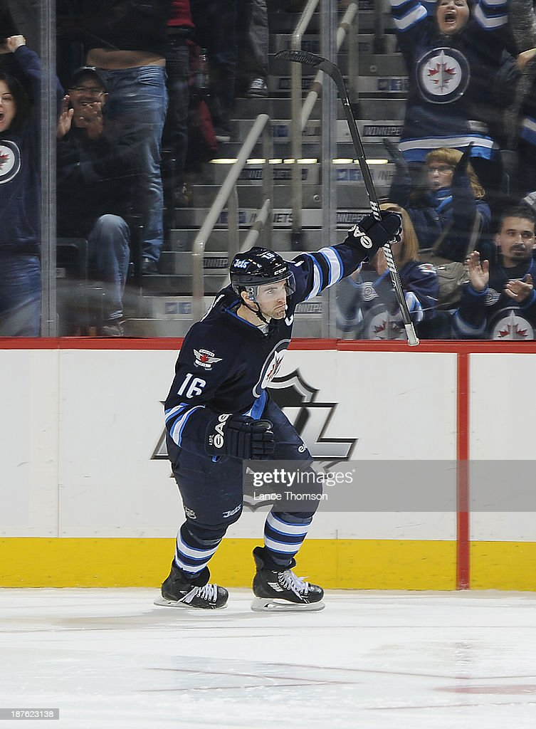 <a gi-track='captionPersonalityLinkClicked' href=/galleries/search?phrase=Andrew+Ladd&family=editorial&specificpeople=228452 ng-click='$event.stopPropagation()'>Andrew Ladd</a> #16 of the Winnipeg Jets raises his stick in celebration after scoring a goal in the shootout against the San Jose Sharks at the MTS Centre on November 10, 2013 in Winnipeg, Manitoba, Canada. The Jets defeated the Sharks 5-4.