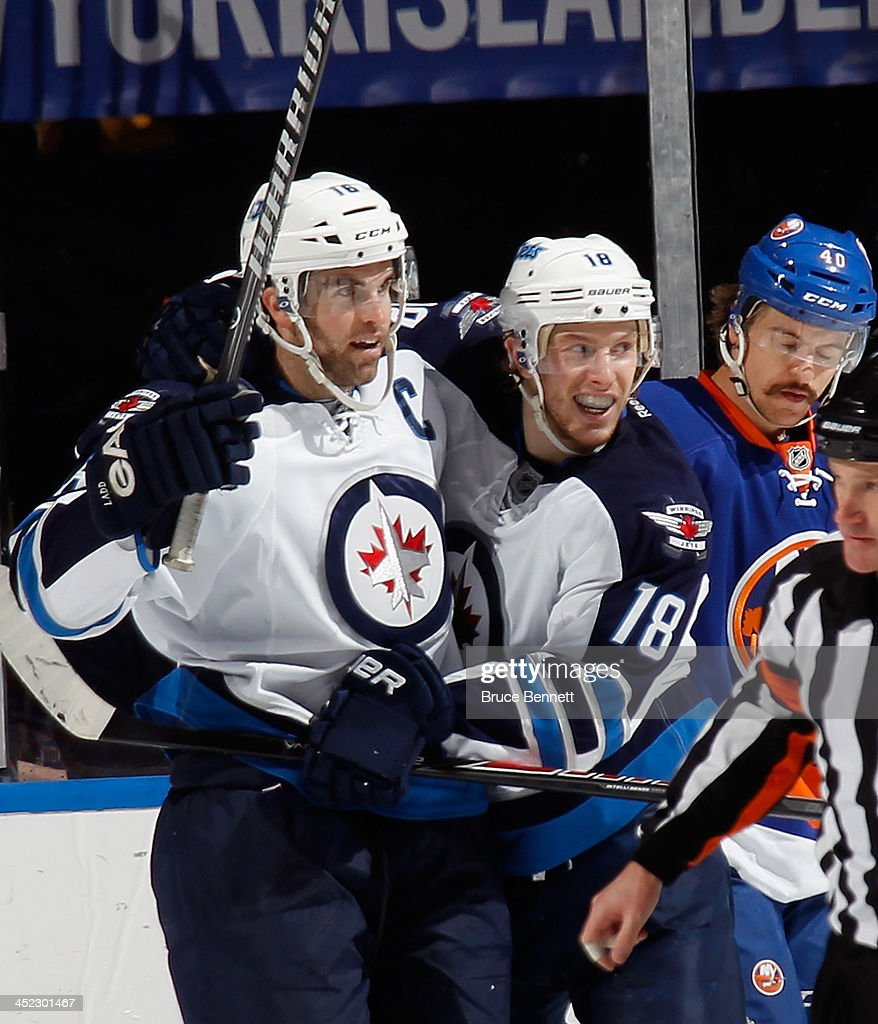 <a gi-track='captionPersonalityLinkClicked' href=/galleries/search?phrase=Andrew+Ladd&family=editorial&specificpeople=228452 ng-click='$event.stopPropagation()'>Andrew Ladd</a> #16 of the Winnipeg Jets (L) scores at 14:39 of the second period against the New York Islanders and is joined by <a gi-track='captionPersonalityLinkClicked' href=/galleries/search?phrase=Bryan+Little&family=editorial&specificpeople=540533 ng-click='$event.stopPropagation()'>Bryan Little</a> #18 (R) at the Nassau Veterans Memorial Coliseum on November 27, 2013 in Uniondale, New York.