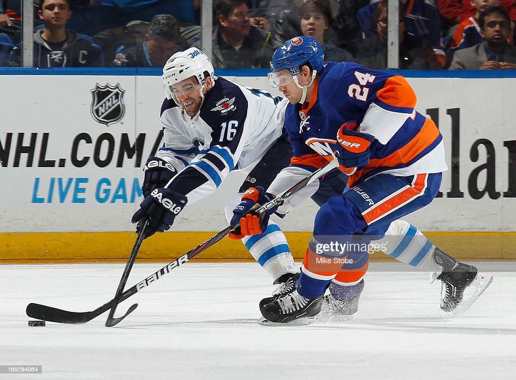Andrew Ladd #16 of the Winnipeg Jets skates against Brad Boyes #24 of the New York Islanders at Nassau Veterans Memorial Coliseum on April 2, 2013 in Uniondale, New York.