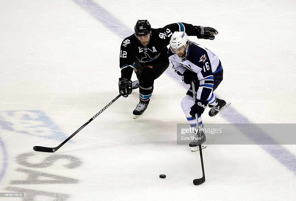 <a gi-track='captionPersonalityLinkClicked' href=/galleries/search?phrase=Andrew+Ladd&family=editorial&specificpeople=228452 ng-click='$event.stopPropagation()'>Andrew Ladd</a> #16 of the Winnipeg Jets skates away from <a gi-track='captionPersonalityLinkClicked' href=/galleries/search?phrase=Patrick+Marleau&family=editorial&specificpeople=203165 ng-click='$event.stopPropagation()'>Patrick Marleau</a> #12 of the San Jose Sharks at SAP Center on March 27, 2014 in San Jose, California.