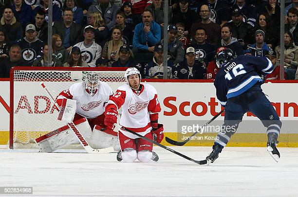 Andrew Ladd of the Winnipeg Jets takes a shot on goal past a defending Brad Richards of the Detroit Red Wings during first period action at the MTS...