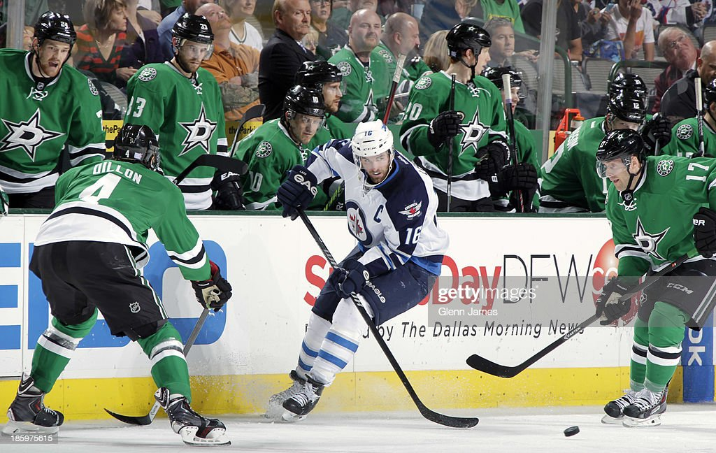 <a gi-track='captionPersonalityLinkClicked' href=/galleries/search?phrase=Andrew+Ladd&family=editorial&specificpeople=228452 ng-click='$event.stopPropagation()'>Andrew Ladd</a> #16 of the Winnipeg Jets tries to keep the puck away from <a gi-track='captionPersonalityLinkClicked' href=/galleries/search?phrase=Rich+Peverley&family=editorial&specificpeople=554442 ng-click='$event.stopPropagation()'>Rich Peverley</a> #17 and <a gi-track='captionPersonalityLinkClicked' href=/galleries/search?phrase=Brenden+Dillon&family=editorial&specificpeople=6254216 ng-click='$event.stopPropagation()'>Brenden Dillon</a> #4 of the Dallas Stars at the American Airlines Center on October 26, 2013 in Dallas, Texas.
