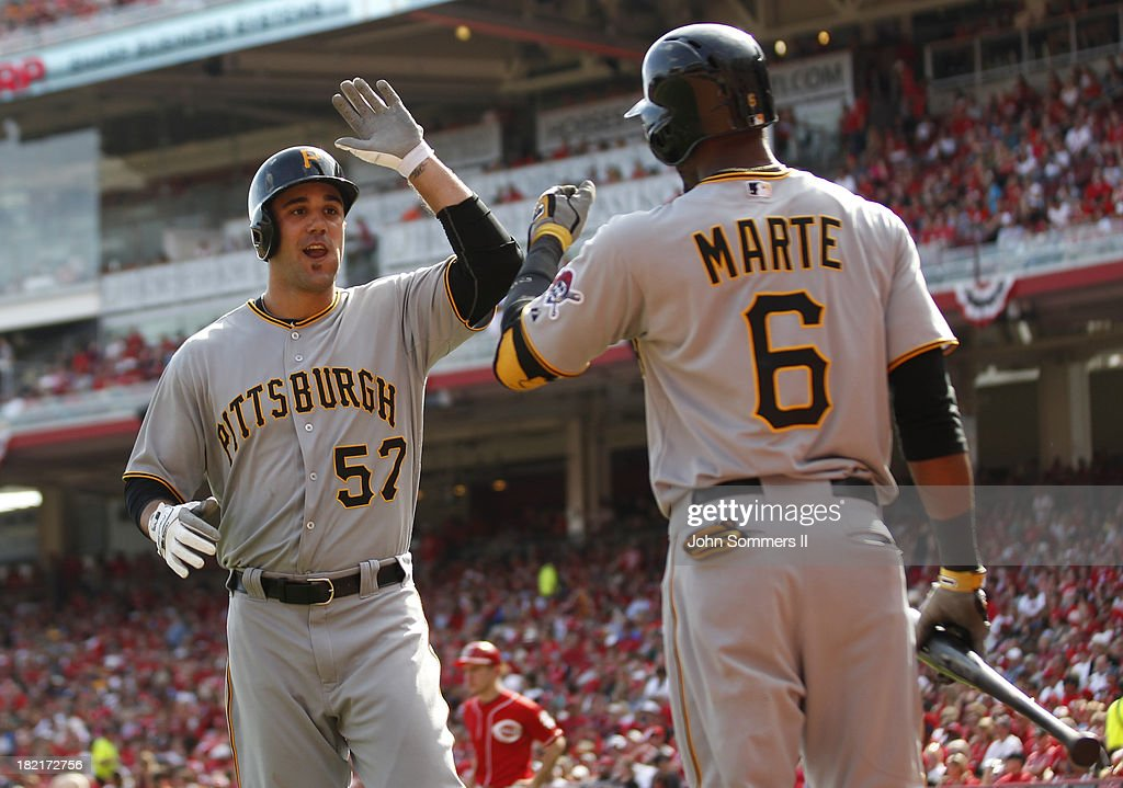 Andrew Lambo #57 celebrates with Starling Marte #6 of the Pittsburgh Pirates after hitting a solo homerun against the Cincinnati Reds at Great American Ball Park on September 28, 2013 in Cincinnati, Ohio.