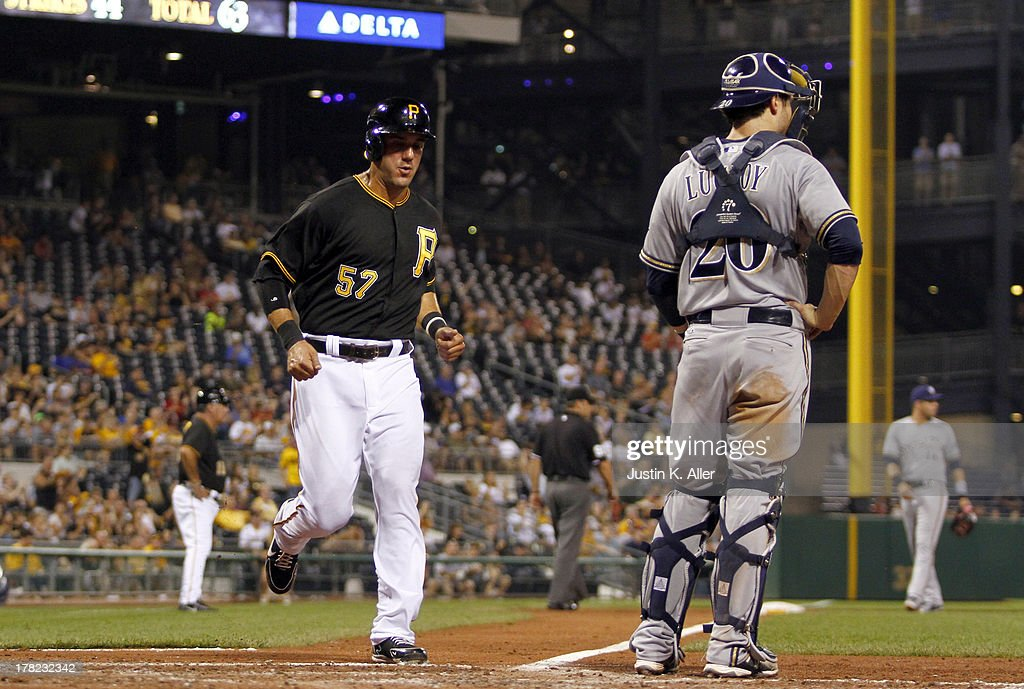Andrew Lambo #57 of the Pittsburgh Pirates scores on an RBI double in the fifth inning by Felix Pie #26 (not pictured) against the Milwaukee Brewers during the game on August 27, 2013 at PNC Park in Pittsburgh, Pennsylvania.