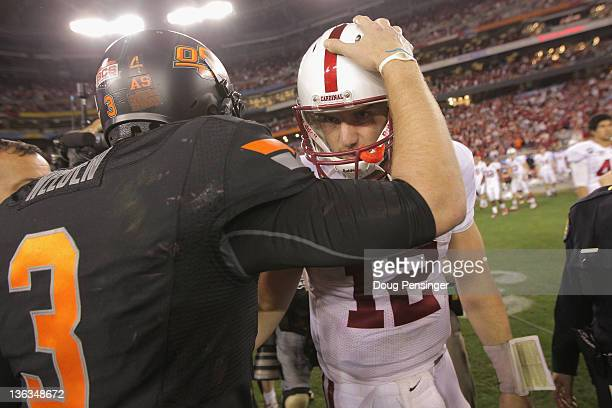 Andrew Luck of the Stanford Cardinal congratulates Brandon Weeden of the Oklahoma State Cowboys after Oklahoma State Cowboys won 4138 in overtime...