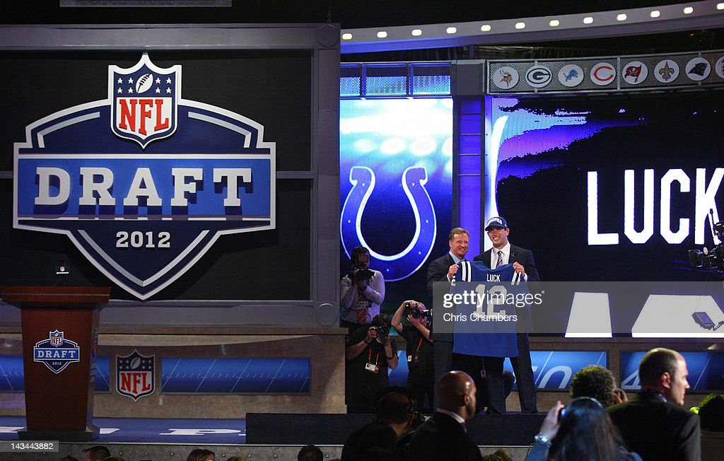 Andrew Luck (R) from Stanford holds up a jersey as he stands on stage with NFL Commissioner Roger Goodell after Luck was selected #1 overall by the Indianapolis Colts in the first round of the 2012 NFL Draft at Radio City Music Hall on April 26, 2012 in New York City.