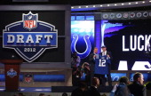 Andrew Luck from Stanford holds up a jersey as he stands on stage with NFL Commissioner Roger Goodell after Luck was selected overall by the...