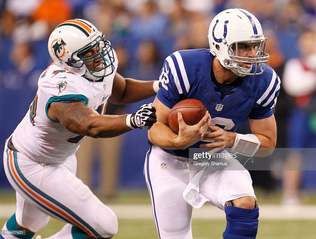 Andrew Luck #12 of the Indianapolis Colts escapes the tackle of Cameron Wake #91 of the Miami Dolphins during a fourth quarter play at Lucas Oil Stadium on November 4, 2012 in Indianapolis, Indiana.