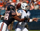 Andrew Luck of the Indianapolis Colts fumbles the ball as he is hit by Corey Wootton of the Chicago Bears during their 2012 NFL season opener at...