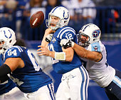 Andrew Luck of the Indianapolis Colts fumbles while being tackled by Karl Klug of the Tennessee Titans at Lucas Oil Stadium on December 1 2013 in...