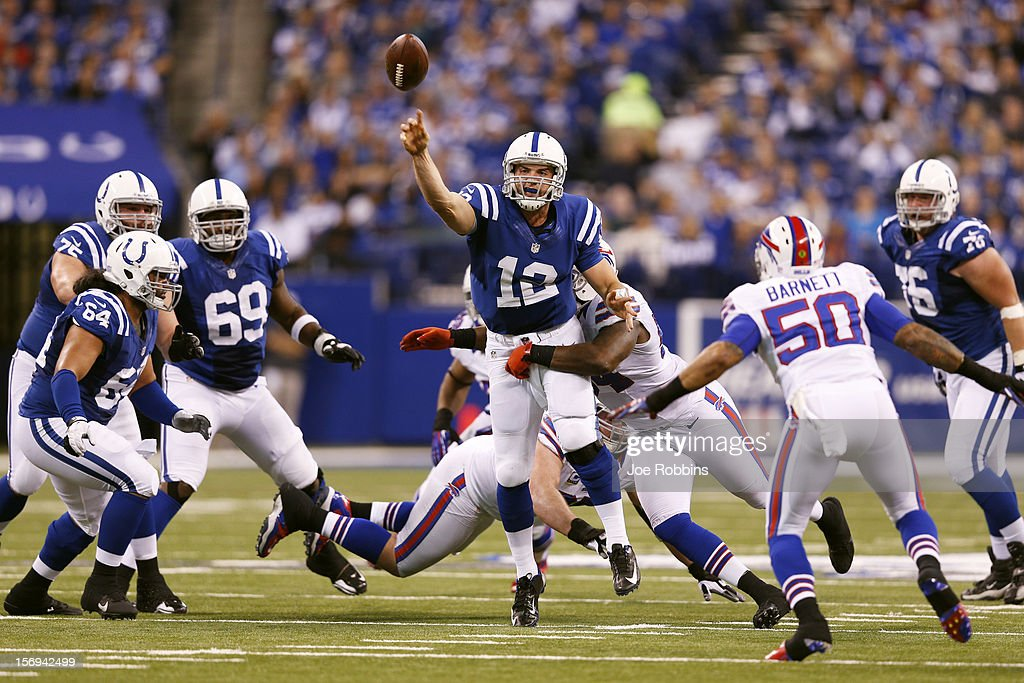 Andrew Luck #12 of the Indianapolis Colts gets a pass off while under pressure against the Buffalo Bills during the game at Lucas Oil Stadium on November 25, 2012 in Indianapolis, Indiana. The Colts won 20-13.