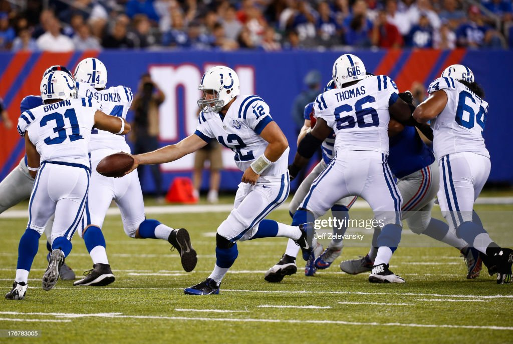 Andrew Luck #12 of the Indianapolis Colts hands off against the New York Giants during their preseason game at MetLife Stadium on August 18, 2013 in East Rutherford, New Jersey.