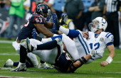 Andrew Luck of the Indianapolis Colts is sacked by JJ Watt and Bradie James of the Houston Texans in the first half of the game at Reliant Stadium on...
