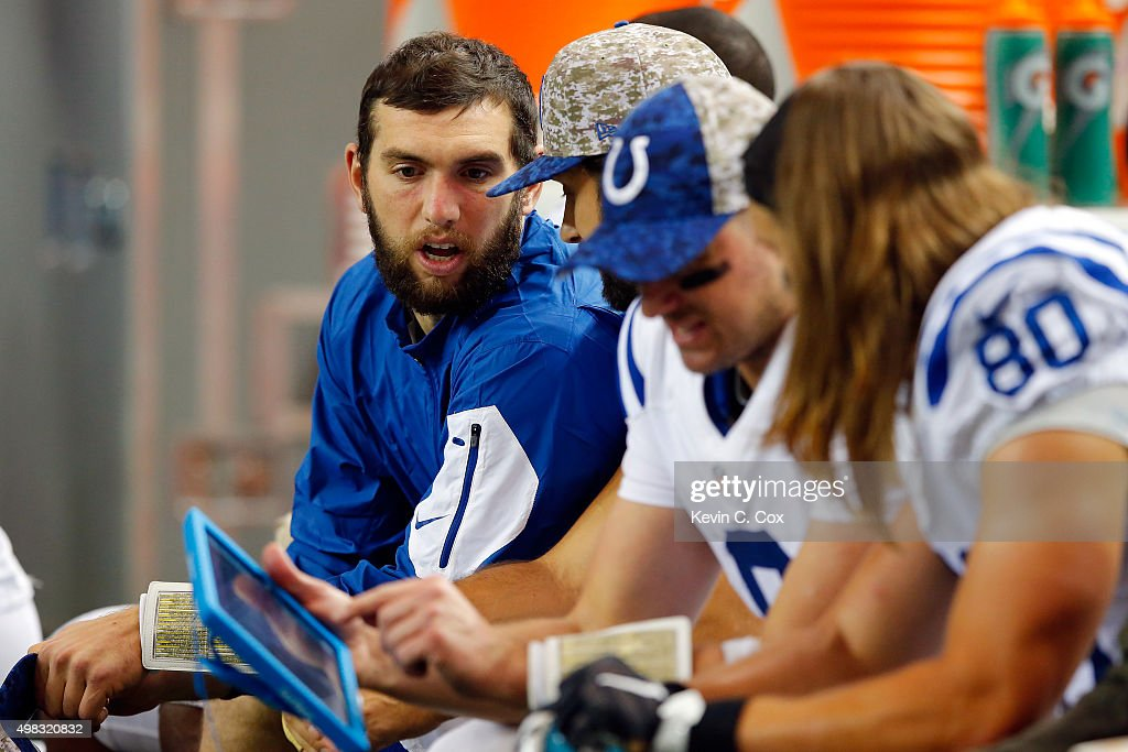 Andrew Luck #12 of the Indianapolis Colts looks at a tablet with his teammates on the sidelines during the second half against the Atlanta Falcons at the Georgia Dome on November 22, 2015 in Atlanta, Georgia.