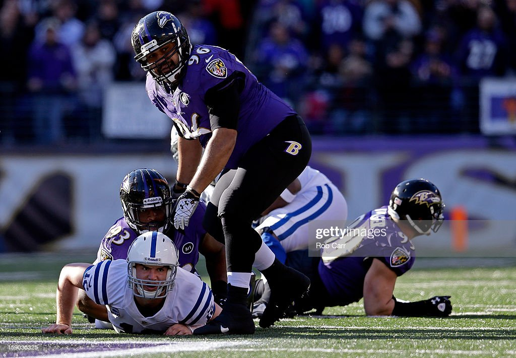 Andrew Luck of the Indianapolis Colts looks up from the turf in the first quarter against DeAngelo Tyson and Ma'ake Kemoeatu of the Baltimore Ravens...
