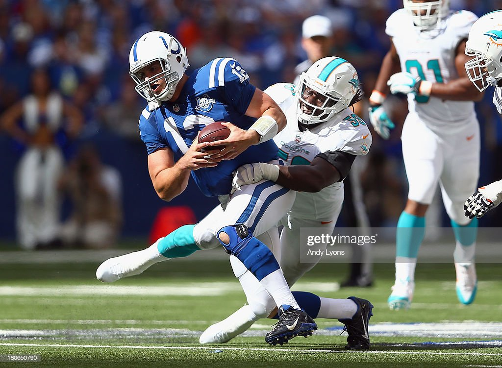 <a gi-track='captionPersonalityLinkClicked' href=/galleries/search?phrase=Andrew+Luck&family=editorial&specificpeople=6258221 ng-click='$event.stopPropagation()'>Andrew Luck</a> #12 of the Indianapolis Colts runs with the ball while being tackled by <a gi-track='captionPersonalityLinkClicked' href=/galleries/search?phrase=Dannell+Ellerbe&family=editorial&specificpeople=4090365 ng-click='$event.stopPropagation()'>Dannell Ellerbe</a> #59 of the Miami Dolphins during the Dolphins 24-20 win at Lucas Oil Stadium on September 15, 2013 in Indianapolis, Indiana.