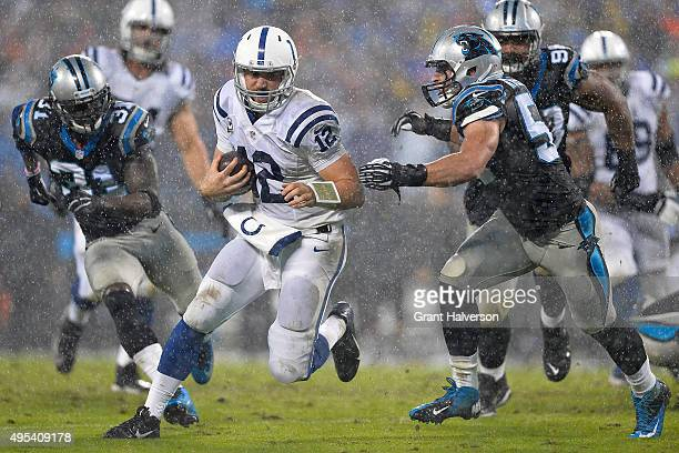Andrew Luck of the Indianapolis Colts scrambles as Luke Kuechly of the Carolina Panthers pursues during their game at Bank of America Stadium on...