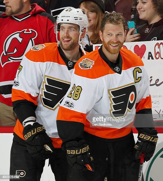 Andrew MacDonald and Claude Giroux of the Philadelphia Flyers share a laugh during warmups prior to their game against the New Jersey Devils on...