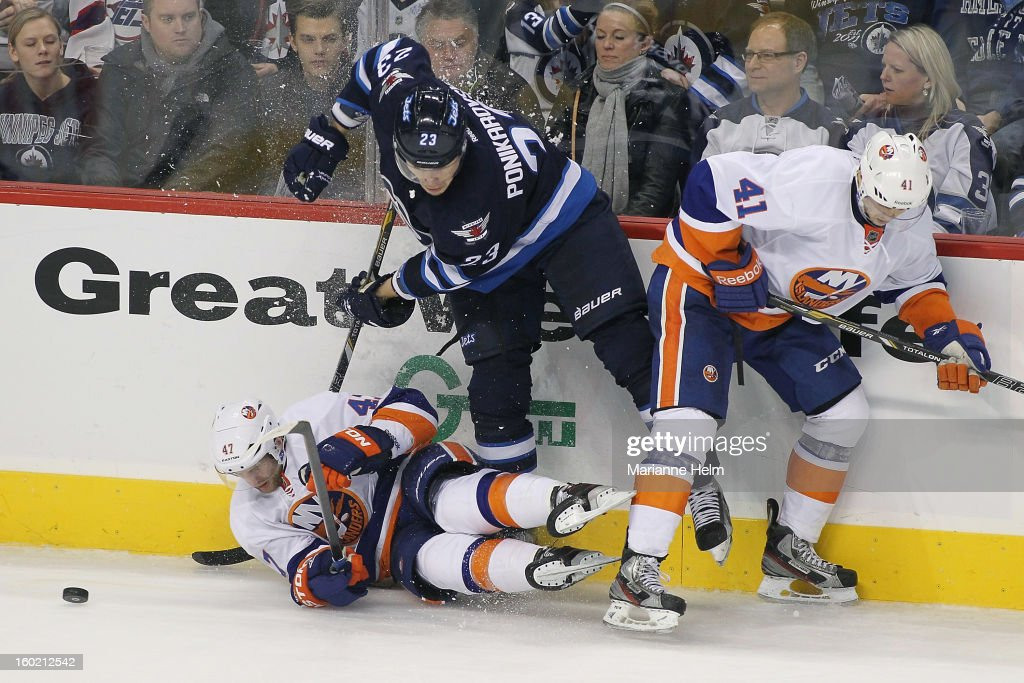 Andrew MacDonald #47 and David Ullstrom #41 of the New York Islanders collide with <a gi-track='captionPersonalityLinkClicked' href=/galleries/search?phrase=Alexei+Ponikarovsky&family=editorial&specificpeople=210628 ng-click='$event.stopPropagation()'>Alexei Ponikarovsky</a> #23 of the Winnipeg Jets against the boards in NHL action on January 27, 2013 at the MTS Centre in Winnipeg, Manitoba, Canada.