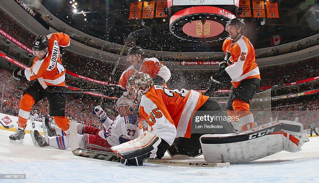 Andrew MacDonald Matt Read and Braydon Coburn of the Philadelphia Flyers defend Steve Mason while Ryan McDonagh of the New York Rangers falls into...