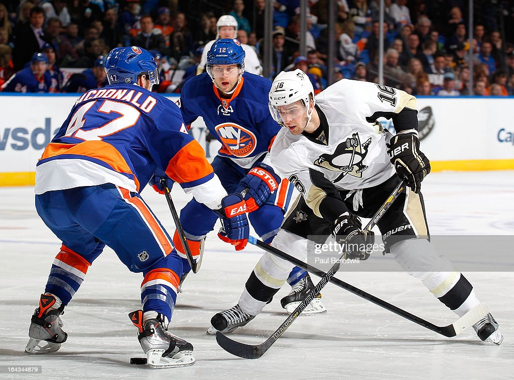 Andrew MacDonald #47 of the New York Islanders and Brandon Sutter #16 of the Pittsburgh Penguins battle for the puck in an NHL hockey game at Nassau Veterans Memorial Coliseum on March 22, 2013 in Uniondale, New York.