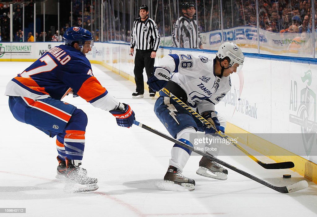 Andrew MacDonald #47 of the New York Islanders attempts to steal the puck from Martin St. Louis #26 of the Tampa Bay Lightning at Nassau Veterans Memorial Coliseum on January 21, 2013 in Uniondale, New York.