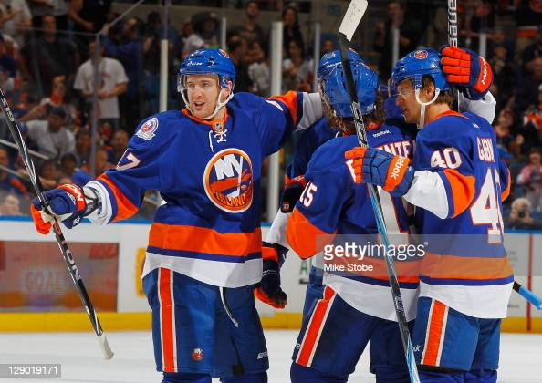 Andrew MacDonald of the New York Islanders celebrates his first period goal with temmates PA Parenteau and Michael Grabner against the Minnesota Wild...
