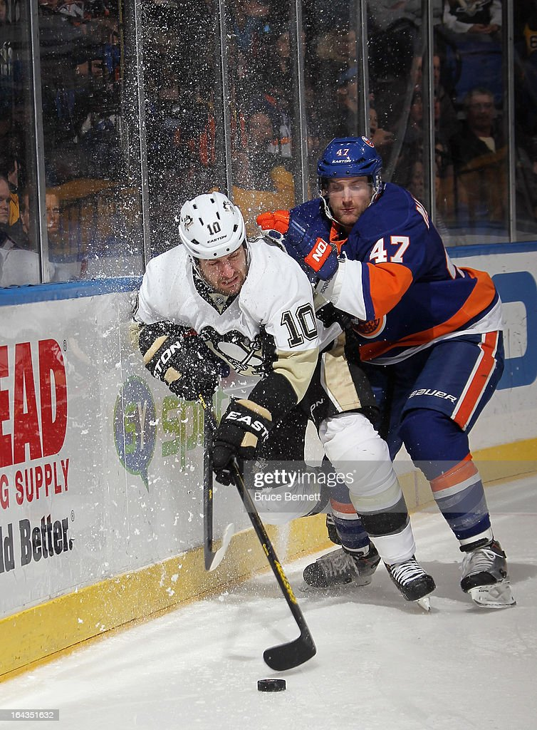 Andrew MacDonald #47 of the New York Islanders checks Tanner Glass #10 of the Pittsburgh Penguins along the boards at Nassau Veterans Memorial Coliseum on March 22, 2013 in Uniondale, New York. The Penguins defeated the Islanders 4-2.