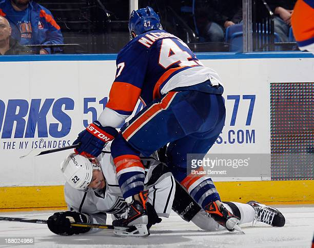 Andrew MacDonald of the New York Islanders checks Trevor Lewis of the Los Angeles Kings during the third period at the Nassau Veterans Memorial...