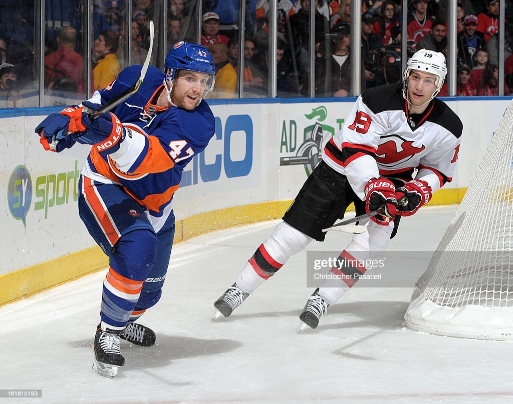 Andrew MacDonald #47 of the New York Islanders clears the puck past Travis Zajac #19 of the New Jersey Devils during the game on February 16, 2013 at Nassau Veterans Memorial Coliseum in Uniondale, New York.
