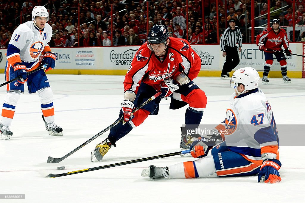 Andrew MacDonald #47 of the New York Islanders goes to the ice while trying to defend against Alex Ovechkin #8 of the Washington Capitals during an NHL game at Verizon Center on April 4, 2013 in Washington, DC.
