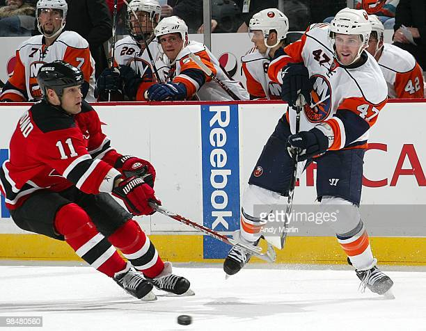 Andrew MacDonald of the New York Islanders plays the puck away from Dean McAmmond of the New Jersey Devils during the game at the Prudential Center...