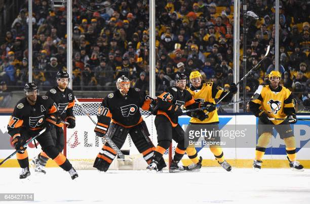 Andrew MacDonald of the Philadelphia Flyers and Tom Kuhnhackl of the Pittsburgh Penguins vie for position next to goaltender Michal Neuvirth of the...