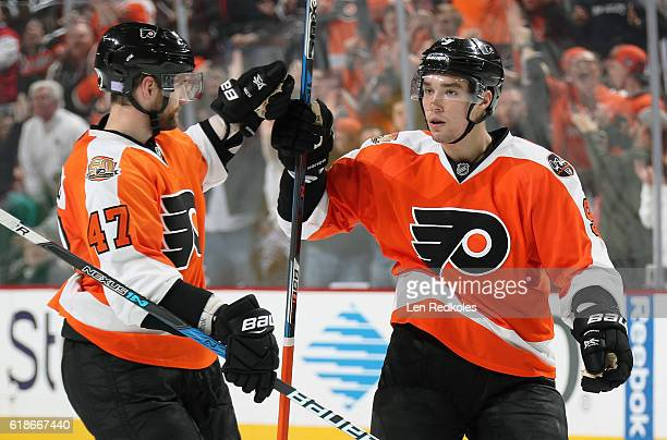 Andrew MacDonald of the Philadelphia Flyers celebrates his third period goal against the Arizona Coyotes with teammate Ivan Provorov on October 27...