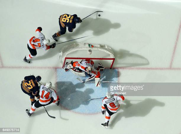 Andrew MacDonald of the Philadelphia Flyers chases Matt Moulson of the Buffalo Sabres behind the net guarded by Steve Mason during an NHL game at the...