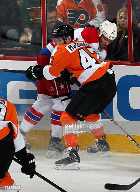 Andrew MacDonald of the Philadelphia Flyers pins Dustin Penner of the Washington Capitals to the boards in the first period on March 5 2014 at the...