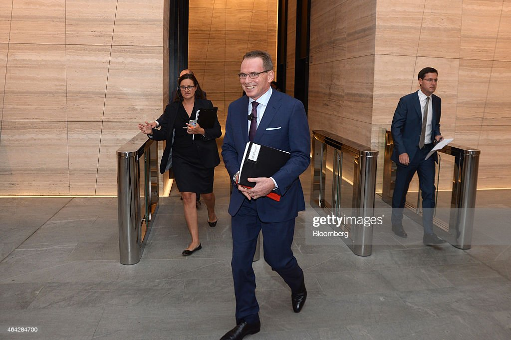 Andrew Mackenzie, chief executive officer of BHP Billiton Ltd., center, smiles after passing through security gates at the company's headquarters ahead of attending an investor briefing in Melbourne, Australia, on Tuesday, Feb. 24, 2015. BHP, the world's biggest mining company, reported better-than-expected first-half earnings as it set out plans to cut project spending to the lowest since 2010. Photographer: Carla Gottgens/Bloomberg via Getty Images