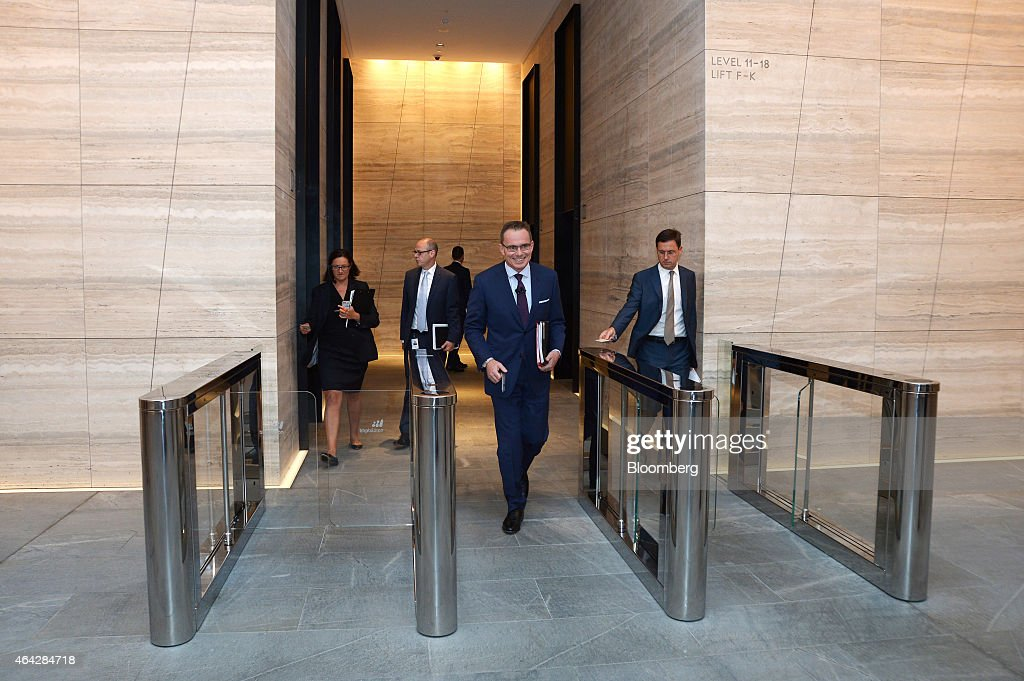 Andrew Mackenzie chief executive officer of BHP Billiton Ltd second right passes through security gates at the company's headquarters ahead of...