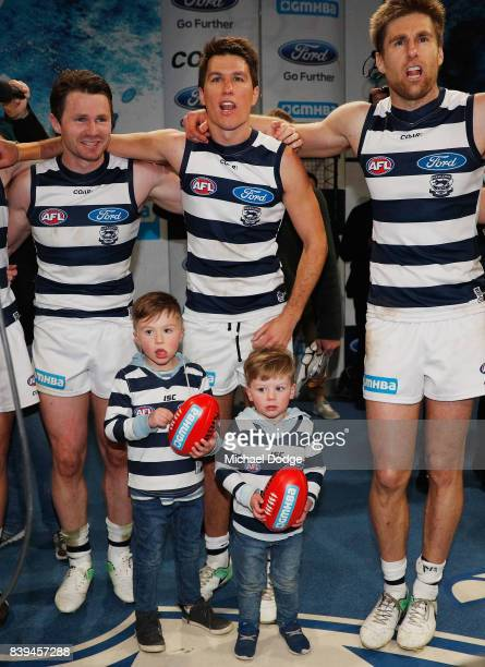 Andrew Mackie of the Cats celebrates with Patrick Dangerfield and Tom Lonergan nd his kids during the round 23 AFL match between the Geelong Cats and...
