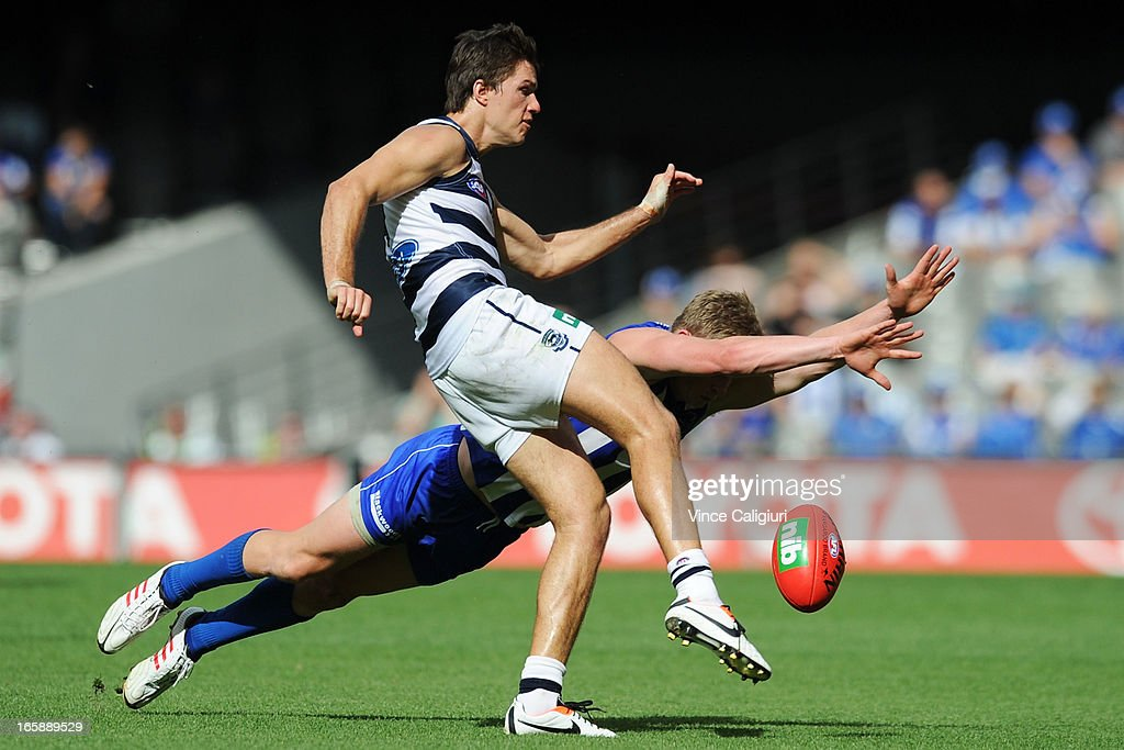 Andrew Mackie of the Cats kicks the ball away from Ryan Bastinac of the Kangaroos during the round two AFL match between the Geelong Cats and the North Melbourne Kangaroos at Etihad Stadium on April 7, 2013 in Melbourne, Australia.
