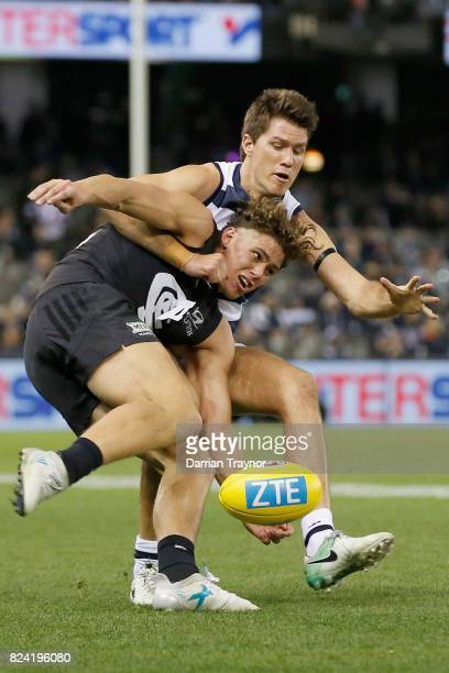 Andrew Mackie of the Cats tackles Charlie Curnow of the Blues during the round 19 AFL match between the Carlton Blues and the Geelong Cats at Etihad...