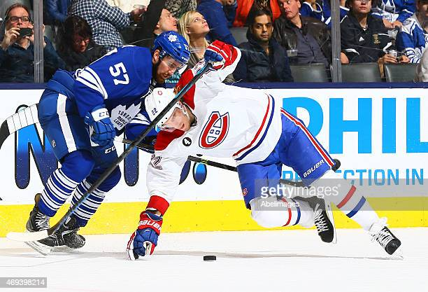 Andrew MacWilliam of the Toronto Maple Leafs knocks down Dale Weise of the Montreal Canadiens during NHL action at the Air Canada Centre April 11...