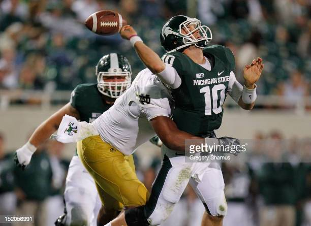 Andrew Maxwell of the Michigan State Spartans fumbles the ball in the fourth quarter while being hit by Stephon Tuitt of the Notre Dame Fighting...
