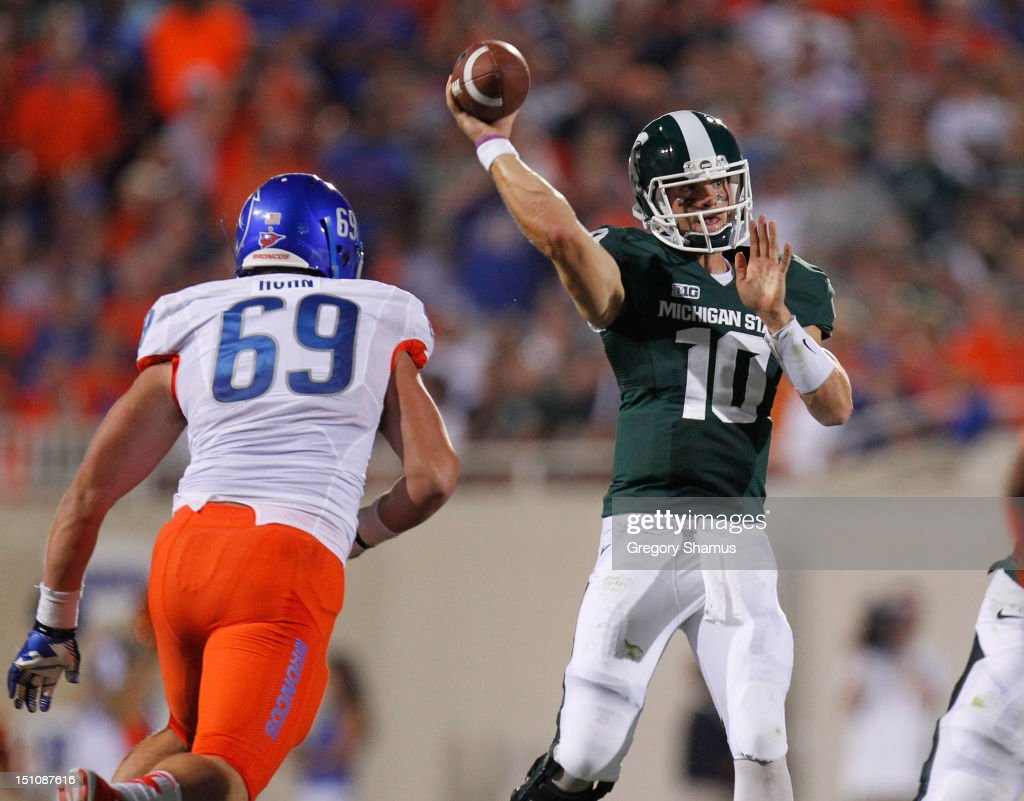 Andrew Maxwell #10 of the Michigan State Spartans passes before being hit by Tyler Horn #69 of the Boise State Broncos at Spartan Stadium on August, 2010 in East Lansing, Michigan.
